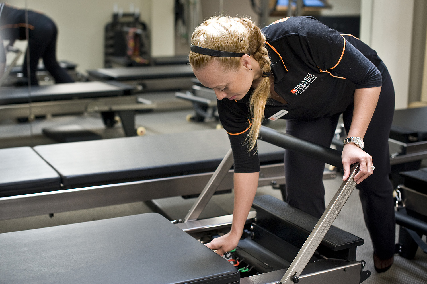 Pilates instructor Venus Brutnall adjusting one of the pilates machines in the studio