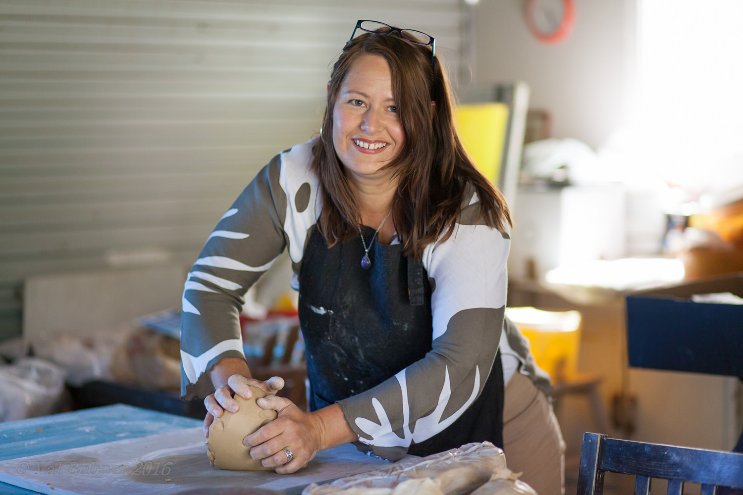 Tania Kunze a ceramic artist from Adelaide kneading clay in her studio