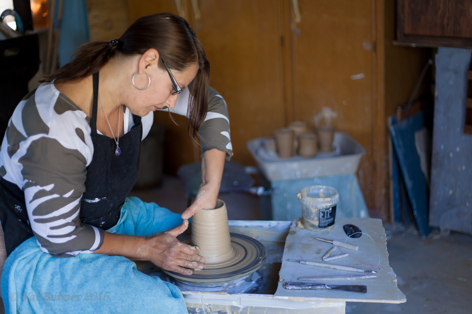 Tania Kunze a ceramic artist from Adelaide shaping a pot on the wheel in her studio